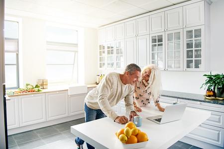カウンターの上に開いているラップトップ コンピューターに面白い何かを見てのカップルと台所のシーン