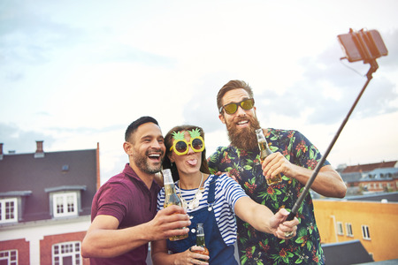 merrymaking: Trio of happy friends with open beer bottles in hand and selfie stick taking a picture of themselves on top of roof in city
