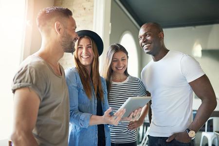 equipo de jóvenes con éxito de los jóvenes modernos entusiastas de pie en la ropa informal en la oficina que tiene una reunión agrupa en torno a una atractiva joven que sostiene una tablilla
