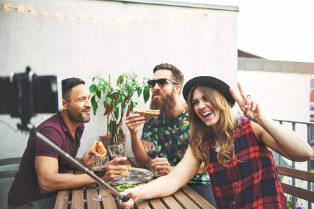 Friends eating pizza and taking pictures with camera on selfie stick outdoors at table Stock Photo
