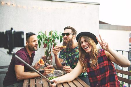 Vrienden eten van pizza en het nemen van foto's met de camera op selfie stok buitenshuis aan tafel