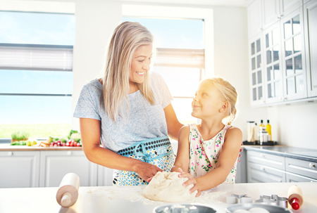 clave sol: Happy young mother and daughter baking together in a high key kitchen backlit by sun flare from the window