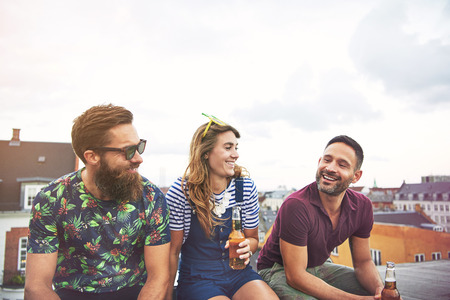 inebriated: Cheerful group of young adults drinking beer from bottles on roof outdoors during summer with copy space in sky Stock Photo