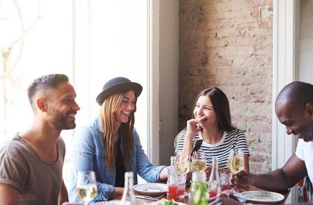 男性と女性の友人やプレートと大きく明るい窓の近くのワイングラスとディナー テーブルで楽しい時間を過ごすカップルのグループ 写真素材