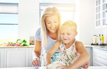 llave de sol: Ni�a adorable amasando la masa vigilado por su madre amorosa mientras aprende a cocinar, fondo clave de alta flama del sol