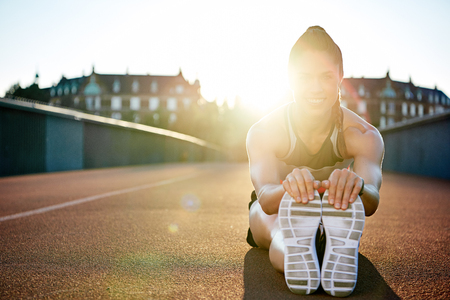 Athlete limbering up before her workout sitting on a tarred bridge doing stretching exercises backlit by a bright early morning sun