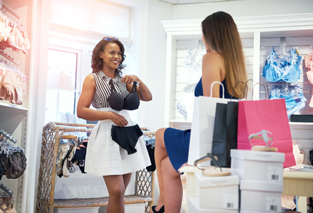 Twee gelukkige chic jonge vrouw winkelen voor lingerie in een kleding boetiek met een bedrijf tot een beha en slipje aan haar lichaam als ze beslissen om te kopen