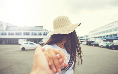 麦わら帽子を身に着けていると、駐車場に立っている間カメラを向けて伸ばした手を持つ女性 写真素材