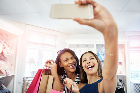 hilarity: Laughing vivacious young women posing for a selfie together in a fashion store as they hold up their purchases in colorful bags