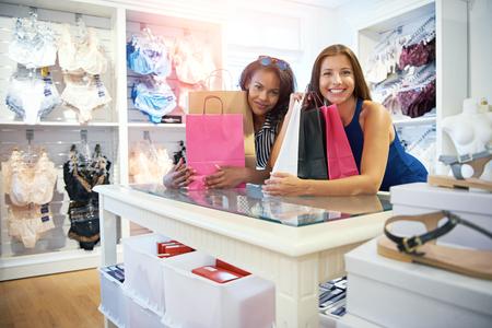 Deux femmes heureux amis shopping pour la lingerie dans une boutique se penchant sur le comptoir avec leurs sacs en attendant de payer