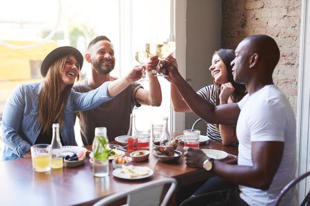 Zwart-witte jonge volwassen koppels vieren met drankjes na het eten bij elkaar aan tafel in restaurant met groot helder raam in de achtergrond