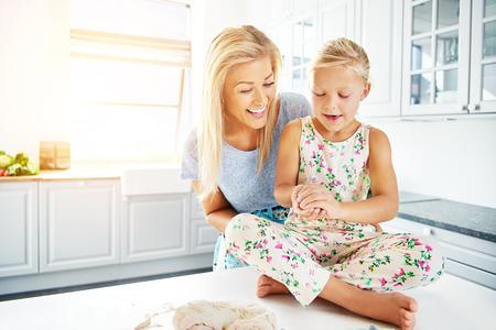 mama e hija: Funcionamiento de la madre con el niño para preparar la masa de pan para hornear en la cocina eléctrica fuerte