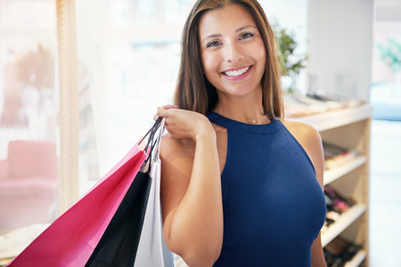 jaunty: Smiling proud young female shopper grinning with pleasure as she stands in a fashion boutique with her shopping bags over her shoulder Stock Photo