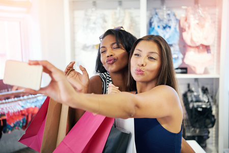 puckering lips: Playful young women flirting with the camera on their mobile phone as they pose for a selfie in a clothing store pouting their lips for a kiss Stock Photo