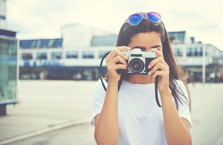 brunette woman: Young woman with her sunglasses perched on her head standing outdoors photographing the camera on a bright summer day Stock Photo