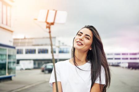 Mooie jonge volwassen vrouw in witte blouse lachend voor de camera op selfie stok tijdens het staan in de straat op bewolkte en winderige dag Stockfoto