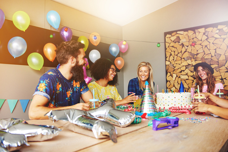 merrymaking: Group of four friends celebrating for a birthday party. Gifts, party decorations and cake on table in front of them.