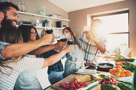 室内の大型キッチン カウンターがあり、食事のための食糧を準備している間ワイン グラスを乾杯する人々 のグループ