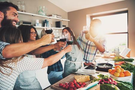 mujeres cocinando: Grupo de personas que tuestan los vidrios de vino mientras se prepara la comida para comer en gran encimera de la cocina en el interior