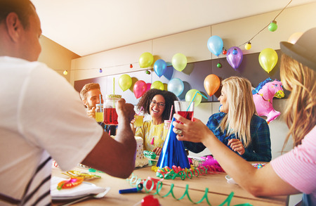 merrymaking: Coworkers laughing during a birthday party. Decorations made from colorful balloons on chalkboard behind them.