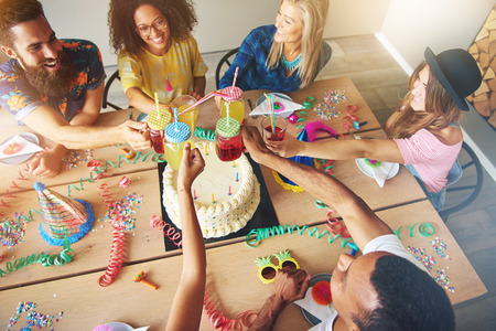 merrymaking: View from above on group of adults sitting at large wooden table around birthday cake