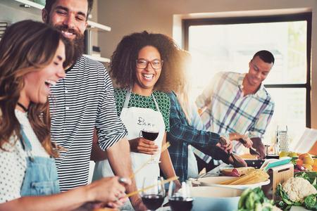 Groep diverse vrienden drinken en koken in de voorkant van de lange voedselbereiding tafel binnen