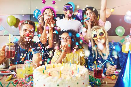 confetti 큰 케이크와 함께 파티를 축 하 하 고 그들의 앞에 테이블에 음료를 그룹 주위 비행
