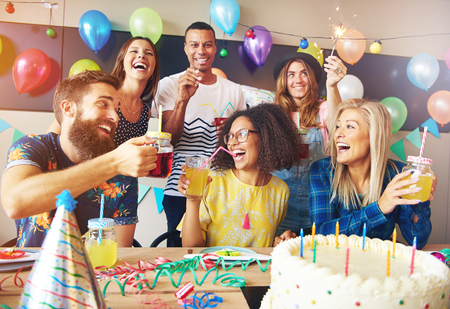 hilarity: Happy exuberant group of friends celebrating a birthday party toasting the birthday girl laughing and joking Stock Photo