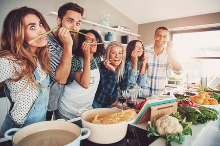 Groep van koks spelen met asperges stelen tijdens het staan in de voorkant van kommen van water, pasta en groenten