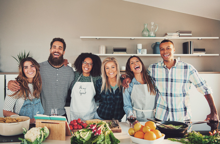 Happy group of six young adults at food preparation table laughing and embracing each other