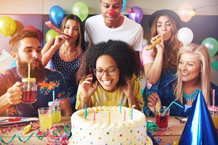 Opgewekte vrouw klaar om te blazen kaarsjes op wit glazuur taart op tafel op verjaardagsfeestje met gelukkige vrienden