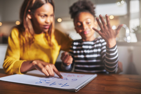sums: School homework concept, mother and daughter calculating