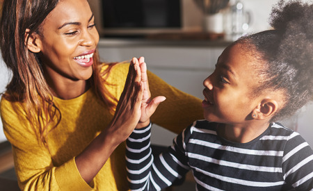 Black mother and child high five in kitchen home Banco de Imagens