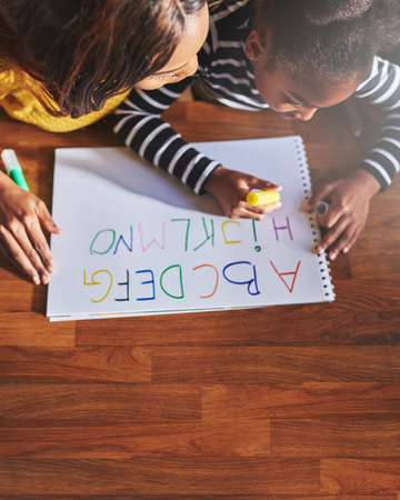 kids writing: Learning the alphabet, overhead view, mom and daughter black