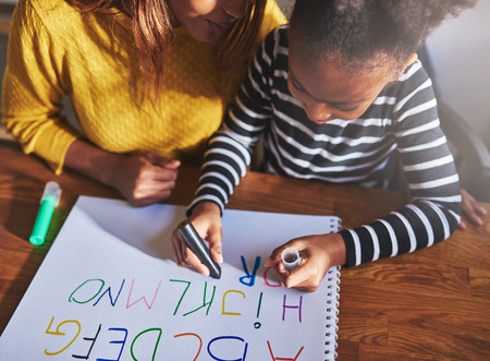 deberes: Overhead view of child learning alphabet at home with mother, black mother and daughter Foto de archivo