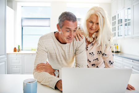 parejas enamoradas: escena de la cocina brillante con pareja de ancianos atractiva mirando algo interesante en su ordenador portátil abierto en conjunto Foto de archivo