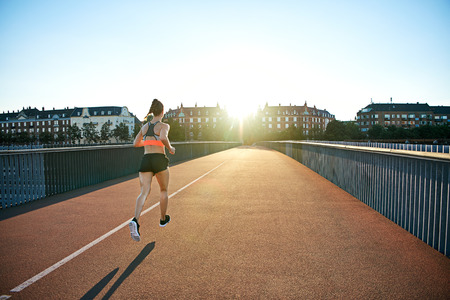 townhouses: Rear view of female athlete jogging down bridge toward bright sunlight reaching over apartment buildings in European city