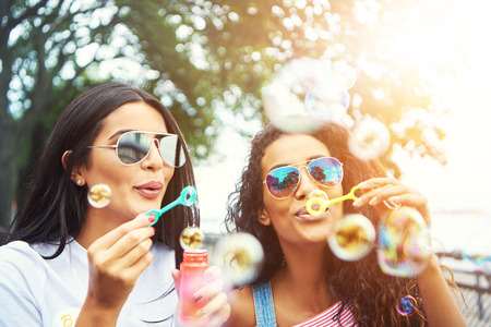Female friends with sunglasses blow bubbles under tall trees as the sun shines overhead