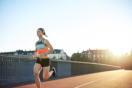 townhouses: Fit muscular young woman runner sprinting across an urban bridge with receding perspective and a bright sunrise with copy space Stock Photo