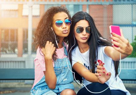 Krásné ženy šklebil vyfotit podle vysoký plot, zatímco nosí sluneční brýle Reklamní fotografie
