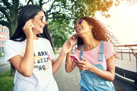ear buds: Laughing female friends listen to music while sharing ear buds on running path