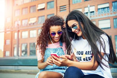 mujeres sentadas: Feliz mujeres jóvenes que comparten tiempo de escucha de música o vídeo en un teléfono de color rosa mientras está sentado fuera
