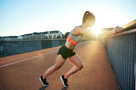 suppleness: Female jogger stretches against bridge railing as sun pokes over her shoulders