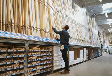 Jonge klusjesman het selecteren van een lengte van gesneden hout uit een rek in een hardware-aanbod magazijn status bereiken voor zijn selectie