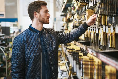 Bebaarde jonge man in een ijzerhandel staan het lezen van de informatie over een product opknoping op het rek, zijaanzicht close-up