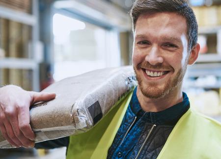 hardware: Sonriente feliz manitas joven guapo o trabajador de almacén con una bolsa de producto por encima del hombro sonriendo a la cámara, vista de cerca