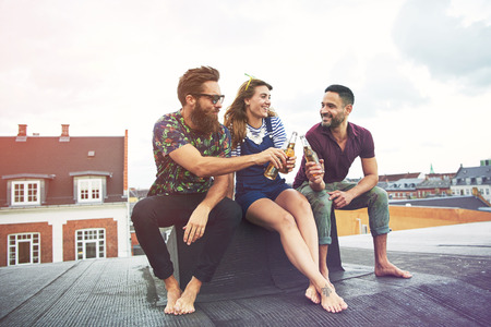 inebriated: Cheerful group of barefoot adults drinking beer on roof outdoors with copy space in sky