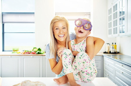 adoring: Laughing little girl wearing huge purple plastic glasses sitting barefoot on the kitchen counter being hugged by her adoring mother Stock Photo