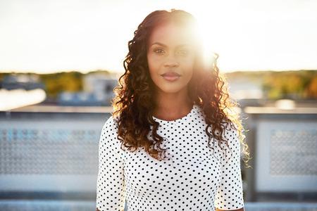 llave de sol: Mujer de Beuatiful de pie alto con el sol detrás brillando detrás de ella al aire libre