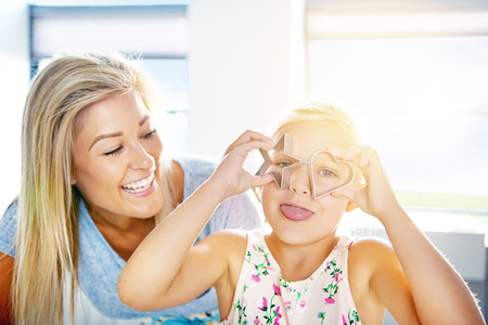 adoring: Cute little girl with pastry cutter glasses sticking out her tongue at the camera watched by her laughing mother Stock Photo